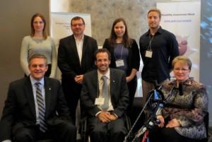 À l'avant, dans l'ordre habituel : le premier ministre Alward, qui est assis sur un fauteuil roulant multisport; Courtney Keenan, président de Capacité Nouveau-Brunswick; et la ministre des Collectivités saines et inclusives, Dorothy Shephard, assise sur un vélo à main. À l'arrière, dans l'ordre habituel : Meaghan Donahue, athlète et coordonnatrice des services d'entraînement, Centre canadien multisport atlantique; Darcy McKillop, directeur général, Sport Nouveau-Brunswick; Sandi Ware, coordonnatrice du service de prêt d'équipement, Para Nouveau-Brunswick; et Gregory Cutler, président du comité des loisirs inclusifs de Recreation New Brunswick.